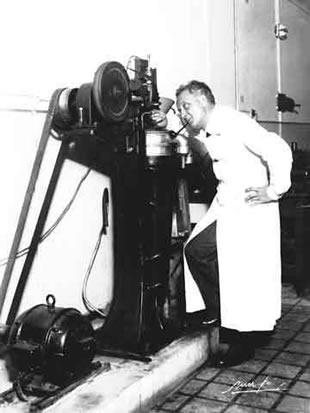 Szent-Györgyi Albert álló, egészalakos képe. A laboratóriumi paprikaőrlő mellett áll, vizsgálódik.